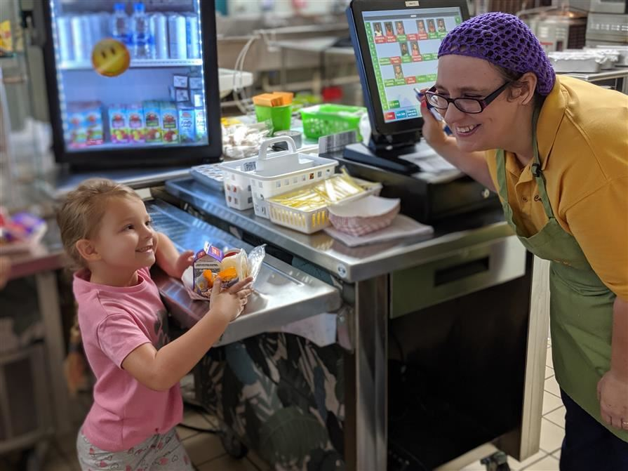 cafeteria worker smiles at student