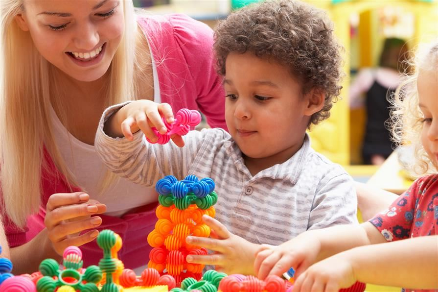 Young child building with plastic toys